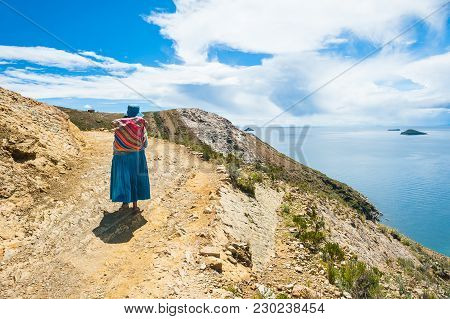 Bolivia - March, 23, 2017. Local Woman In National Clothing Walking On Island Of Sun (isla Del Sol)