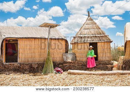 Titicaca Lake, Puno, Peru - March, 20, 2017. Woman In Traditional Dresses On Uros Floating Islands O