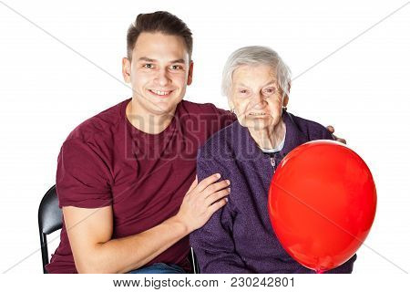 Picture Of A Smiling Grandmother And Her Cheerful Grandson Embracing And Holding A Red Balloon