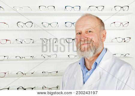 Smiling Mature Ophthalmologist Wearing White Uniform In Optical Store