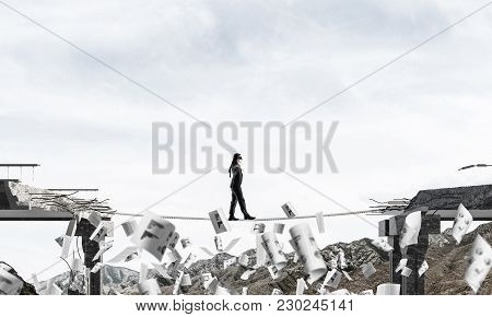 Businessman Walking Blindfolded On Rope Among Flying Papers And Above Huge Gap In Bridge As Symbol O