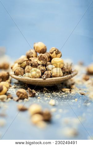 Close Up Of Baked Or Roasted Chickpea/channa Or Dalia In A Bowl On A Blue Surface.