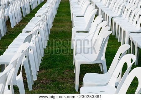 White Plastic Chairs Pattern Row On The Garden For An Outdoor Event.