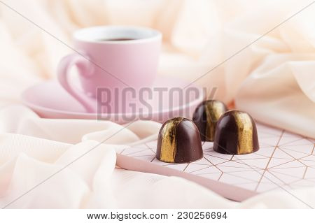 Luxury Bonbons With Cup Of Coffee On Pastel Pink Background
