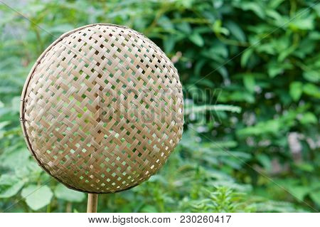 Brown Wicker Bamboo Basket Hanging On Bamboo Stick Have Blur Green Leaves As Background With Copy Sp