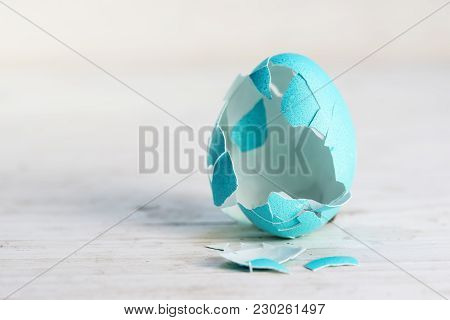 Broken Empty Easter Egg In Turquoise On A White Painted Wooden Background, Concept For Today's Tradi
