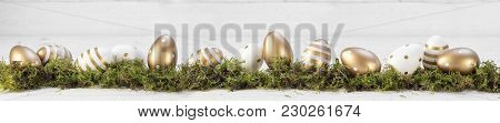 Easter Decoration, Gold Painted Eggs On Moss Against A Gray White Wooden Background, Extra Wide Pano