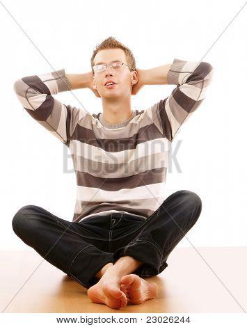 Porträt des entspannten junger Mann sitzen auf dem Boden. isoliert