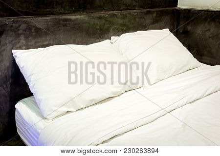 White Pillows On A Bed And Bedding Sheets On The Bed