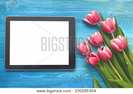 Tulip Flowers And Tablet Computer Device With Blank Screen On Blue Wooden Table Board Background Wit