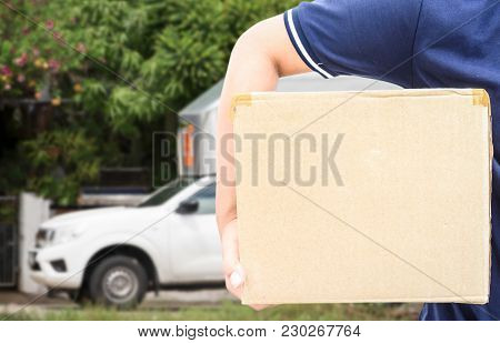Delivery Man In Blue Uniform Holding The Box