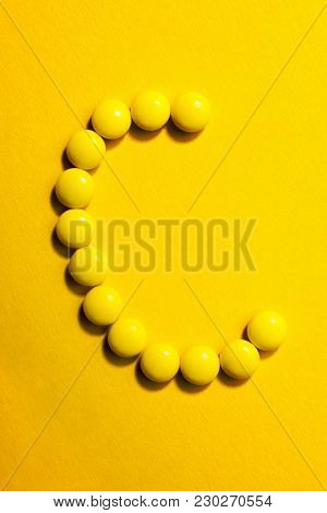 Top View Of  Letter C Made Of Yellow Pills On Yellow Background. Medicine Vitamin C Concept.