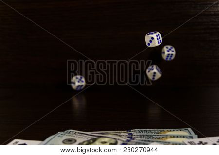 Dice In Flight Above The One Hundred Dollar Bills And Playing Cards. Gamble Concept