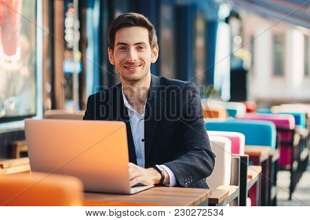Smiling Modern Entrepreneur Working On Laptop Sitting At The Table In A Colorful Cafe. Ambitious Fre
