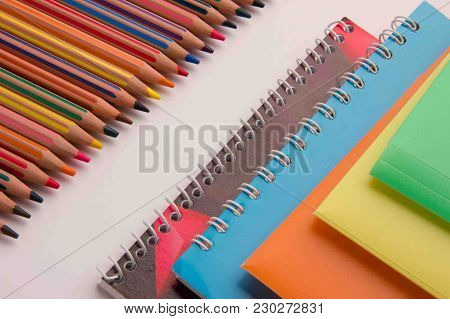 Colored Pencils Folders For Documents And Notebooks On A Spring On An Office White Desk