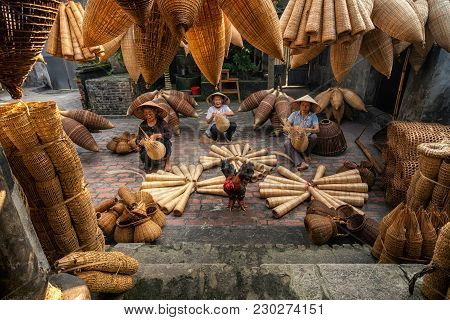 Old Vietnamese Female Craftsman Making The Traditional Bamboo Fish Trap Or Weave At The Old Traditio