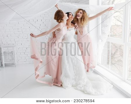 Laughing Bride And Bridesmaids Play In White Studio Room Standing Under Veil.