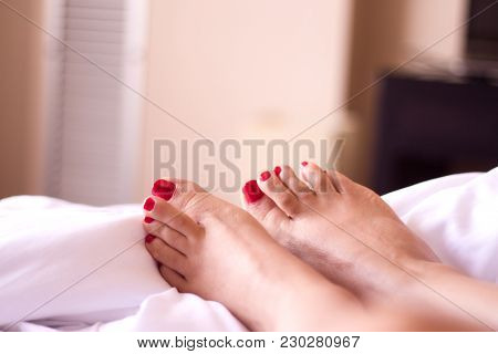 Womans Feet On The Bed Undone. Nails Painted Red