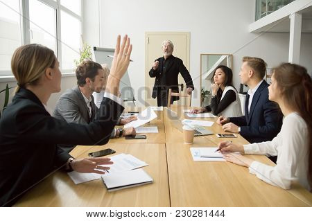 Businesswoman Raising Hand Up At Diverse Team Meeting Sitting At Conference Table, Student Asking Se