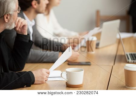 Attentive Senior Businessman Holding Documents Focused On Listening At Group Meeting, Aged Experienc
