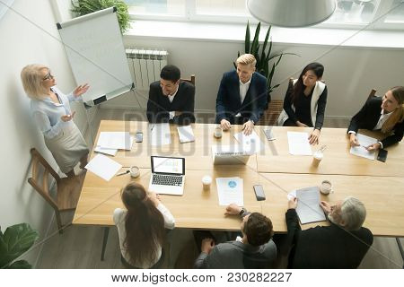 Aged Senior Businesswoman Giving Presentation At Multiracial Group Office Meeting, Female Team Leade