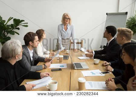 Serious Aged Businesswoman Leading Corporate Team Meeting Talking To Multiracial Employees, Senior F