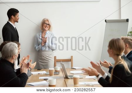 Smiling Senior Businesswoman Boss And Team Clapping Hands At Meeting, Happy Woman Executive Applaudi