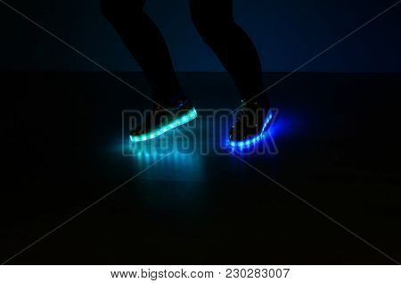 Fashionable Sneakers With Neon Led Lighting On The Legs Of A Girl With Blue And Azure Colors In The