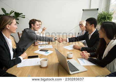 Diverse Businessmen Shaking Hands After Signing Contracts At Group Multiracial Meeting, African And