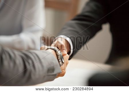 Two Businessmen In Suits Shaking Hands At Group Meeting, Partners Handshaking At Negotiations Making