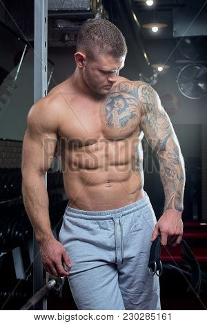 Muscular Shirtless Shredded Strong Man With Blue Eyes And Tattoo Poses In A Gray Pants In A Gym
