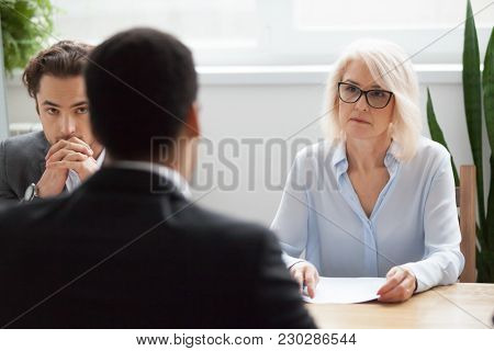 Serious Attentive Senior Female Hr Manager Employer Listening To Candidate At Job Interview, Focused