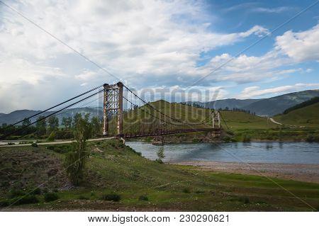 Suspension Bridge Across Mountain River, Evening Light, Blue Sky
