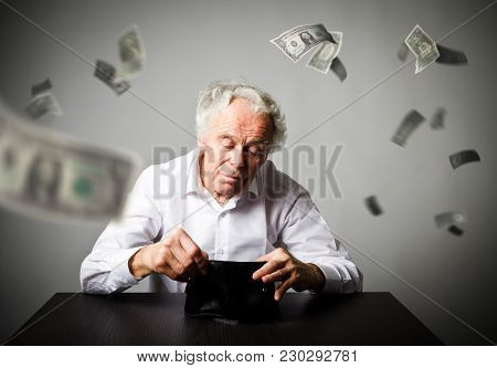 Old Man In White And Empty Wallet. Accounting And Taxes Concept. Falling Dollars.