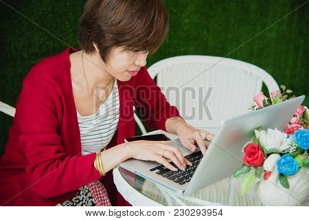 Young Asian Beautiful Woman With Smiling Face Working Outdoor In A Public Park. Working On Laptop Ou