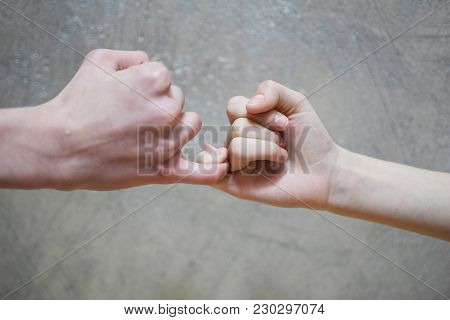 Pinky Swear Handshake Of Teenage Brother And Sister On Blure Grey Brown Wall Background.