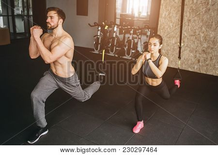 Attractive And Slim Woman And Man Are Doing Lunges On One Leg And Keeping Hands Together In Front Of