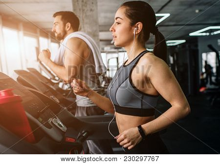 Young Man And Woman Are Running On The Running Machine. They Do This Exercise Every Time They Come T