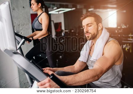 Close Up Of A Guy Wokring On The Exercise Bike And His Girfriend Doing The Same Thing Further Down.