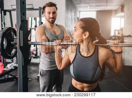 Close Up Of A Girl Wants To Have Some Squats In Smith's Machine. She Is Looking To Her Trainer Becau