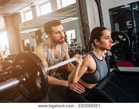 A Picture Where Guy Is Helping And Supporting Her Girlfriend To Do Squats In Smith's Machine. They A