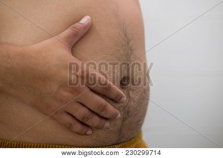 Asian Fat Man Has Cholesterol. He Shows Excess Fat Of The Tummy