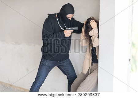 Black Masked Robber In Black Long Sleeve Shirt Is Holding A Gun And Intimidate A Woman,he Is Pulling