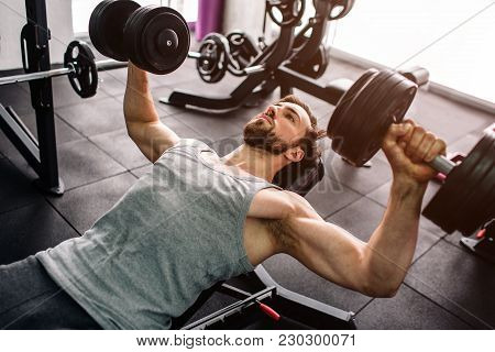 Close Up Of A Strong Man Doing Push Ups With The Dumbells. He Is Consentrated Only On Doing That Exe