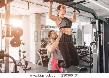 Trainer and his student is in the gy. He is helping her to pull up. THis is a part of big list of exercises poster