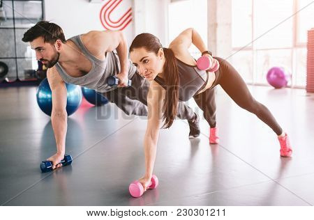 Good Picture Of Boy And Girl Standing On The Carpet With The Dumbells In One Hand And Putting Anothe