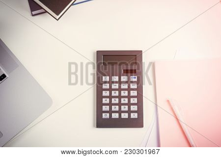 Office Desk Or Business Workstation With An Open Laptop, Journals Calculator And Notepad With Pen Vi