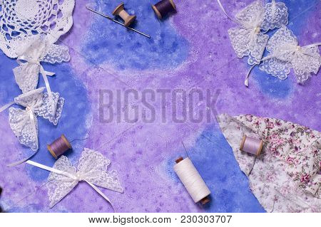 Frame With Spools, Sewing Threads, Lace Bows On Abstract Purple Background