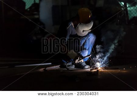 Low Light Image Of Welder Or Craftsman In A Welding Mask And Welders Leathers, A Metal Product Is We