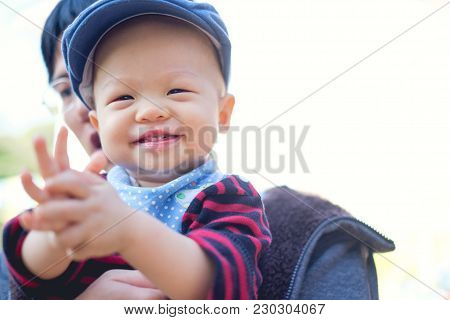 Asian Father Holding Happy Toddler Baby Boy Smiling Wearing Sweater, Bib, Hat Clapping Hands At Gard